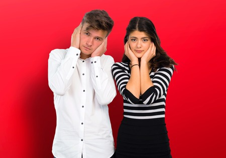 Young couple covering both ears with hands