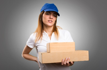 Delivery woman with back pain on grey background Standard-Bild