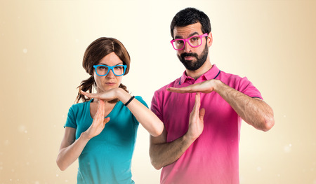 Couple in colorful clothes making time out gesture Foto de archivo