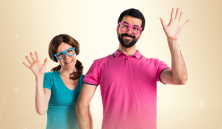 Couple in colorful clothes saluting