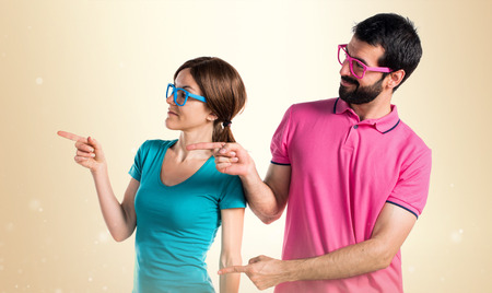 Couple in colorful clothes pointing to the lateral Banco de Imagens