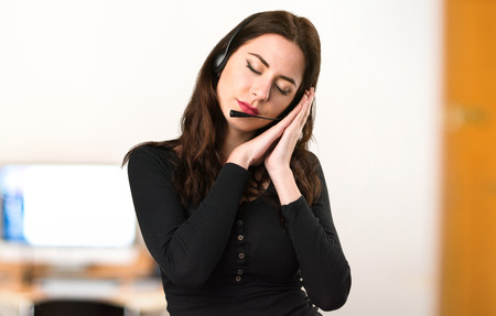 Telemarketer Beautiful young girl making sleep gesture in the office