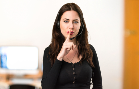 Telemarketer Beautiful young girl making silence gesture in the office