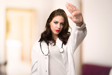 Doctor woman making stop sign on unfocused background