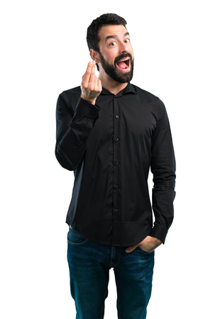 Handsome man with beard making money gesture on white background