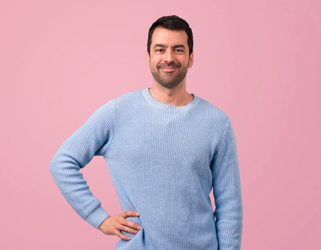 Handsome man posing with arms at hip on pink background