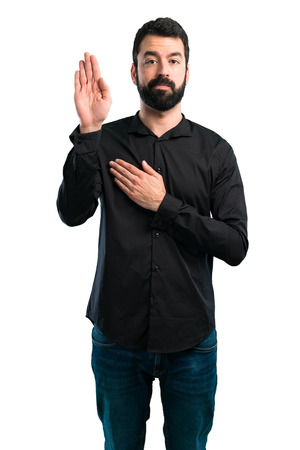 Handsome man with beard making an oath on white background