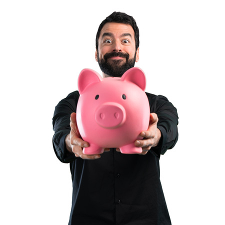 Handsome man with beard holding a piggybank on white background