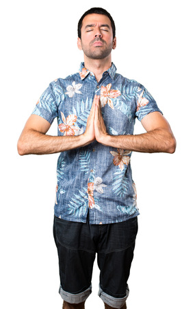 Handsome man with flower shirt in zen position on isolated white background Stock Photo
