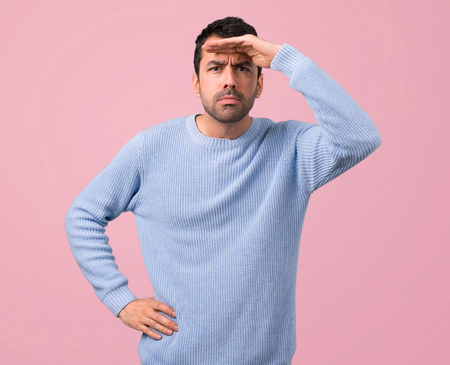Man with blue sweater looking far away with hand to look something on pink background
