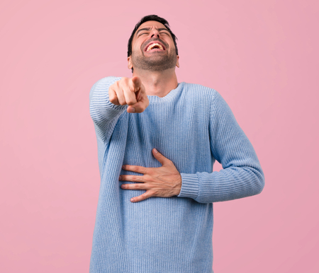 Handsome man pointing with finger at someone and laughing a lot on pink background