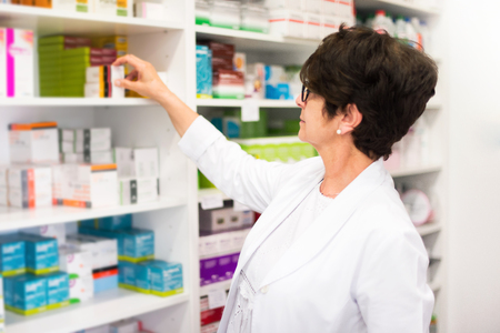 Middle-aged woman customer in the pharmacy looking for medications
