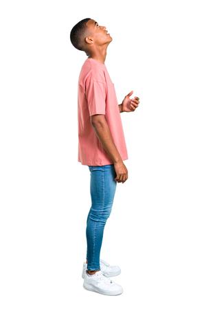 Stand di giovane uomo afroamericano in piedi e alzando lo sguardo su sfondo bianco isolato. Ideale per l'uso in progetti architettonici