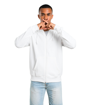 Dark-skinned young man with white sweatshirt showing a sign of closing mouth and silence gesture on isolated white background