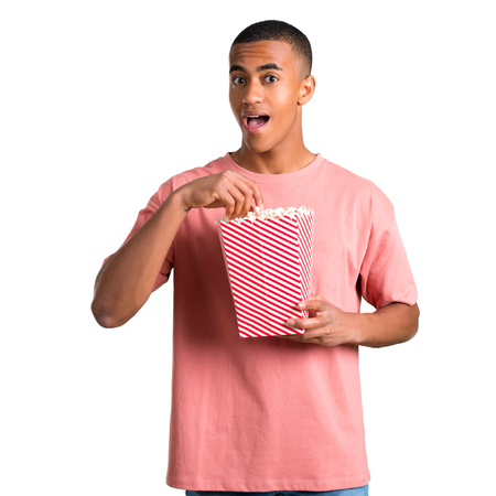 Young african american man eating popcorns in a big bowl on isolated white background