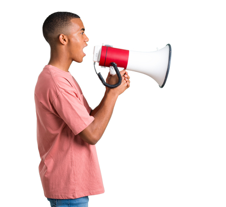 Young african american man shouting through a megaphone to announce something in lateral position on isolated white background