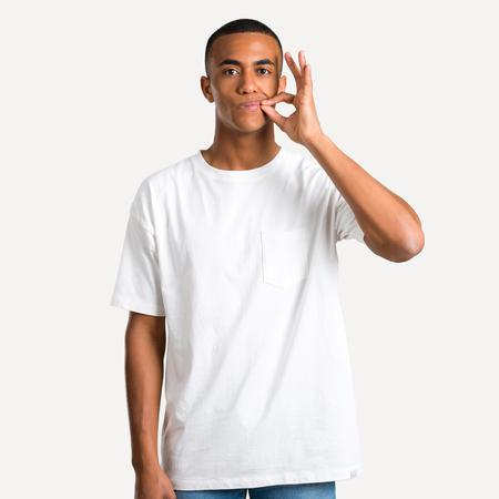 Young african american man showing a sign of closing mouth and silence gesture doing like closing his mouth with a zipper on isolated background 免版税图像