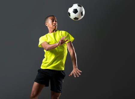 Soccer player man with dark skinned playing hitting head on dark background