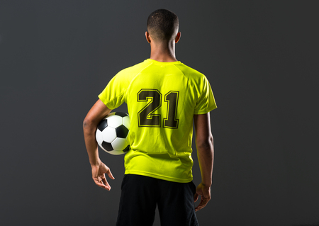 Soccer player man with dark skinned playing catching a ball with his hands on dark background