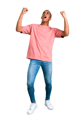 Standing young african american man celebrating a victory and happy for having won a prize on isolated white background