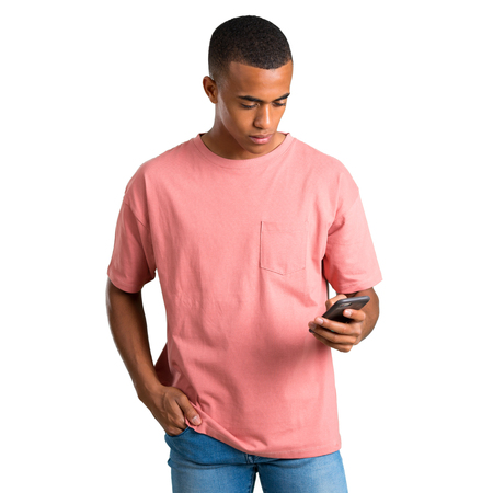 Young african american man sending a message or email with the mobile on isolated white background Stock Photo