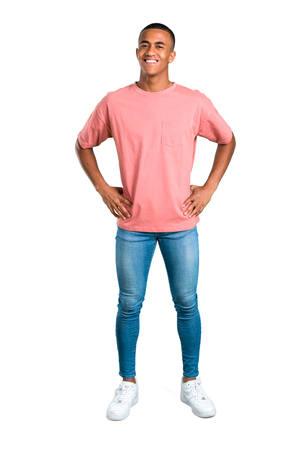 Standing young african american man posing with arms at hip on isolated white background