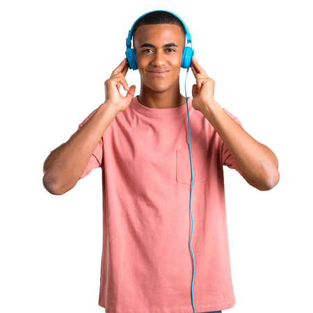 Young african american man listening to music with headphones on isolated white background Stock Photo