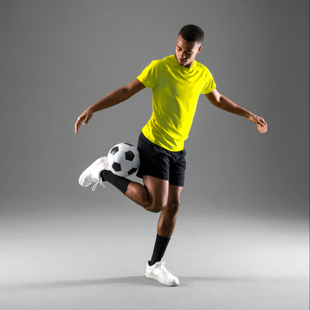 Soccer player man with dark skinned playing on dark background Stock Photo