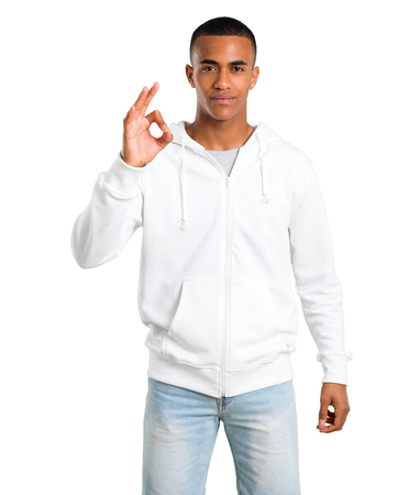 Dark-skinned young man with white sweatshirt showing an ok sign with fingers. Face of happiness and satisfaction on isolated white background