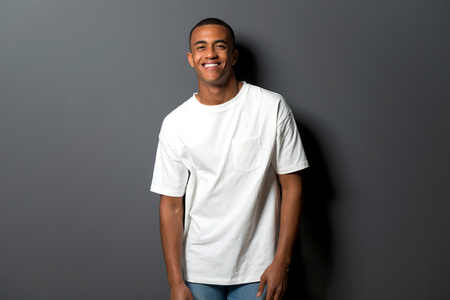 Happy young african american man on grey wall background Stock Photo