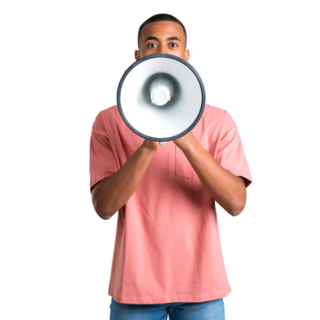 Young african american man shouting through a megaphone to announce something on isolated white background Stock Photo