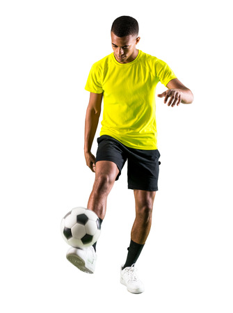 Soccer player man with dark skinned playing kicking the ball on isolated white background