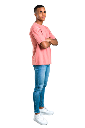 Standing young african american man keeping the arms crossed in lateral position while smiling. Confident expression on isolated white background. Ideal for use in architectural designs Stock Photo