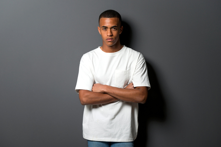 Young african american man on grey wall background with his arms crossed