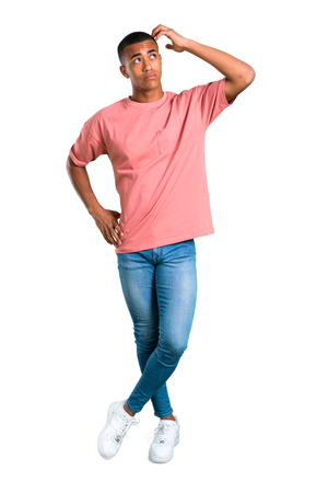 Standing young african american man having doubts and with confuse face expression while scratching head on isolated white background