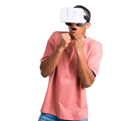 Young african american man using VR glasses. Virtual reality experience on isolated white background