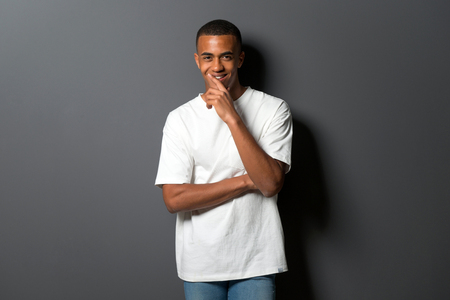 Young african american man on grey wall background thinking