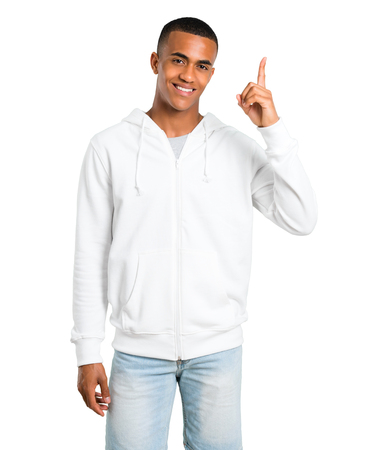 Dark-skinned young man with white sweatshirt showing and lifting a finger in sign of the best on isolated white background