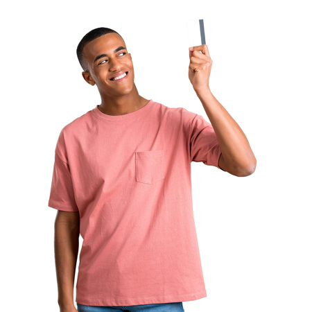 Young african american man holding a credit card and thinking on isolated white background