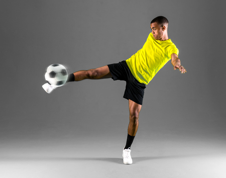 Soccer player man with dark skinned playing kicking the ball on dark background Stock Photo