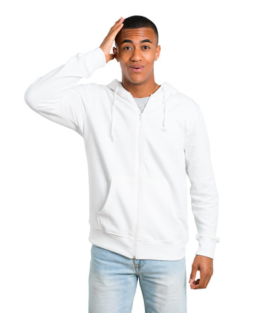 Dark-skinned young man with white sweatshirt enjoy dancing while listening to music at a party on isolated white background