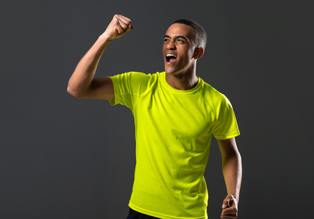Soccer player man with dark skinned playing celebrating victory on dark background