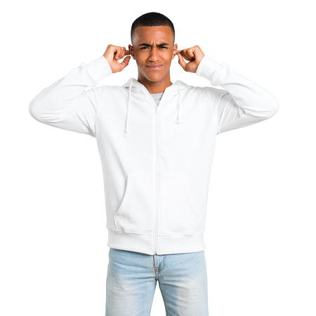 Dark-skinned young man with white sweatshirt covering both ears with hands. Frustrated expression on isolated white background