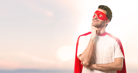 Superhero man with mask and red cape standing and thinking an idea while looking up on a sunset background
