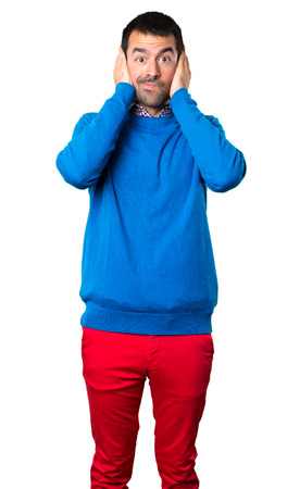 Handsome young man covering his ears on white background