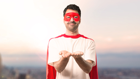 Superhero man with mask and red cape holding copyspace imaginary on the palm to insert an ad on a sunset background Stock Photo