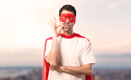 Superhero man with mask and red cape showing a sign of closing mouth and silence gesture doing like closing his mouth with a zipper on a sunset background Stock Photo