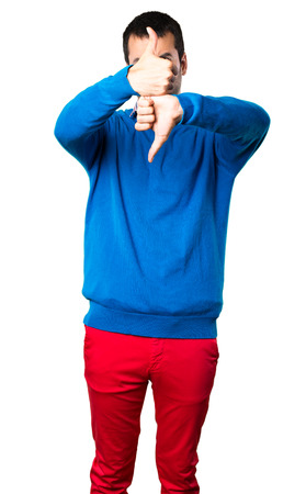 Handsome young man making good-bad sign on white background