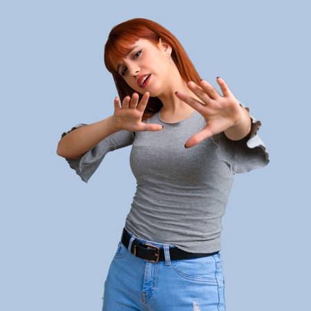 Young redhead girl is a little bit nervous and scared on blue background Stock Photo