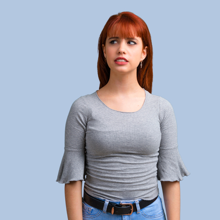 Young redhead girl is a little bit nervous and scared on blue background